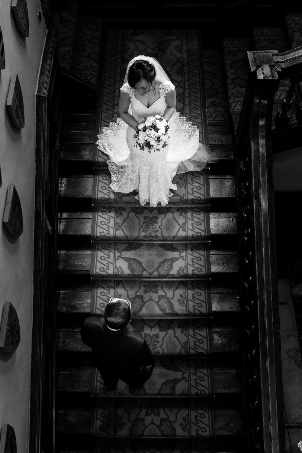 The bride, lit up by the sunlight, stands just behind her father on the stairs of Askham Hall.