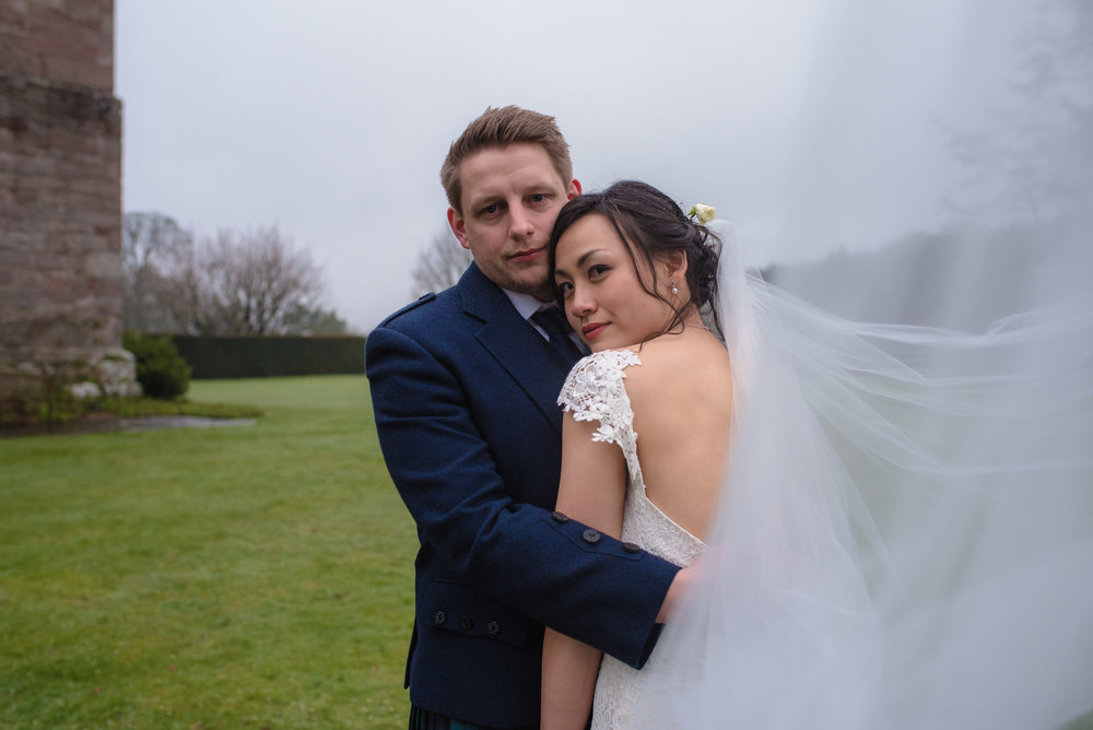 The bride and groom cuddle together during their wedding photography portraits.