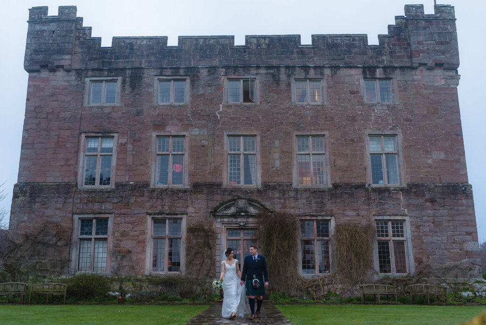 The whole of Askham Hall in view with the bride and groom standing in front of it.
