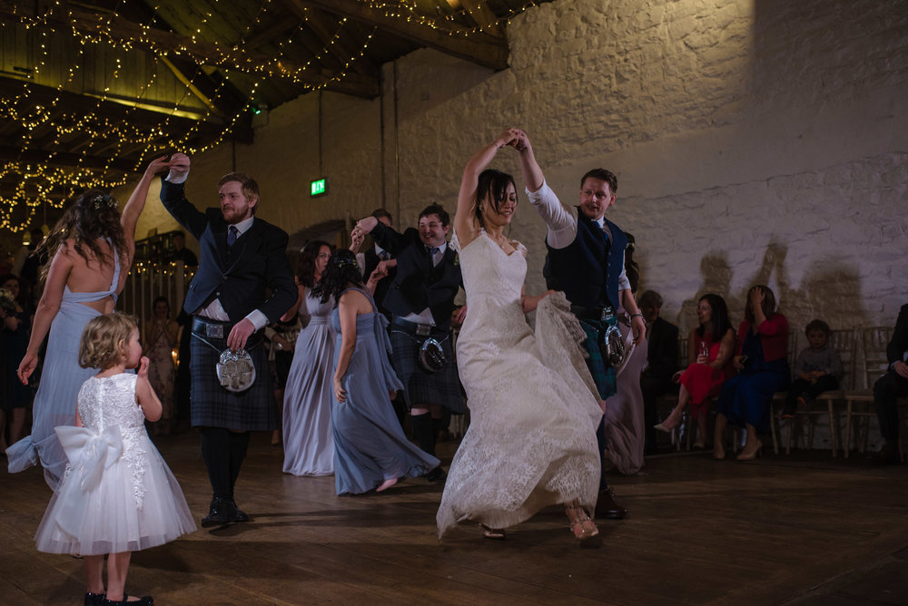 The bride and groom share their first dance with all their guests on the dance floor.