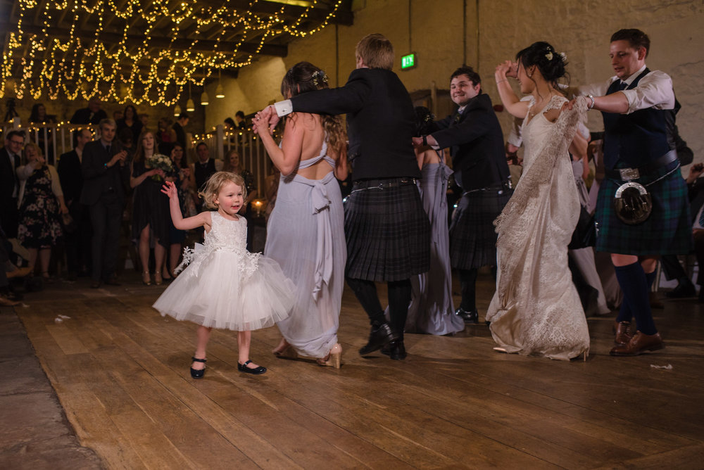 Bridesmaid and the flower girl have a dance together on the dance floor.