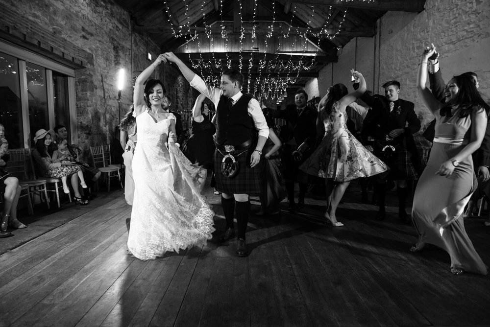 Black and white photo of the bride and groom dancing the gay Gordon's.