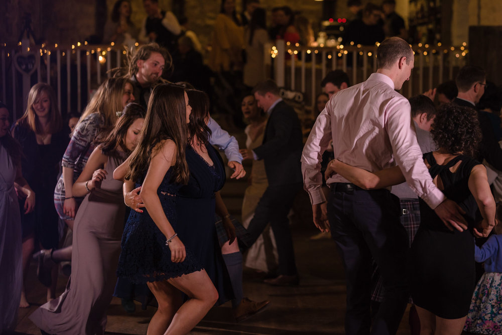 Guests smiling and laughing while dancing some Scottish country dancing.