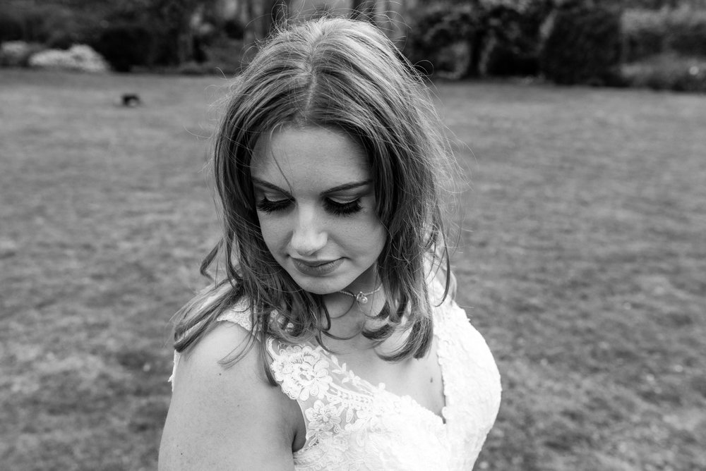 Black and white image of the bride looking down towards the ground.