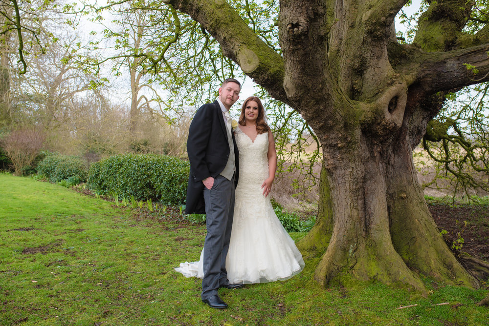 Bride and groom stand under a tree at crabwall manor.