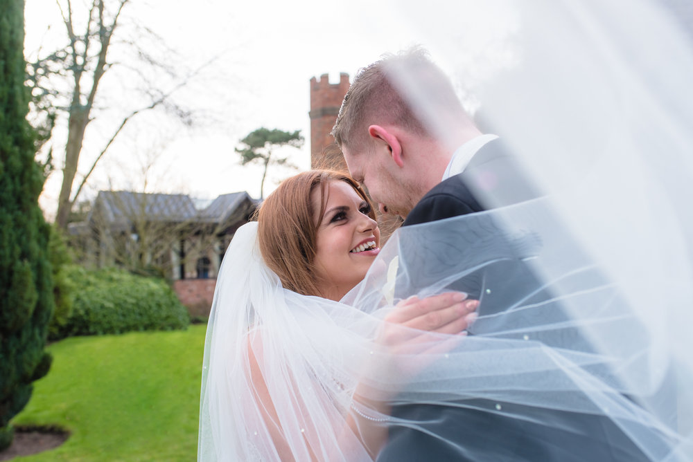 The brides veil partially covers her face as she smiles to her husband.