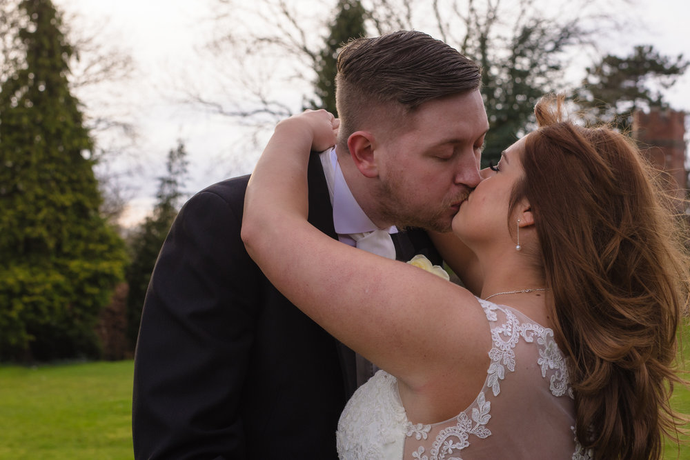 The bride and groom share a kiss together outside crabwall manor.