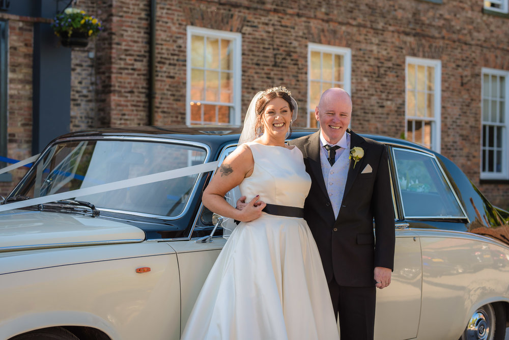 The happy couple with the bridal car