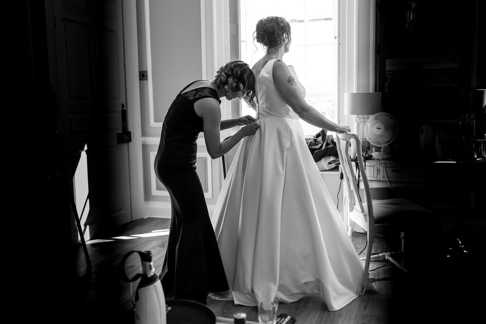 Bride is zipped into her dress
