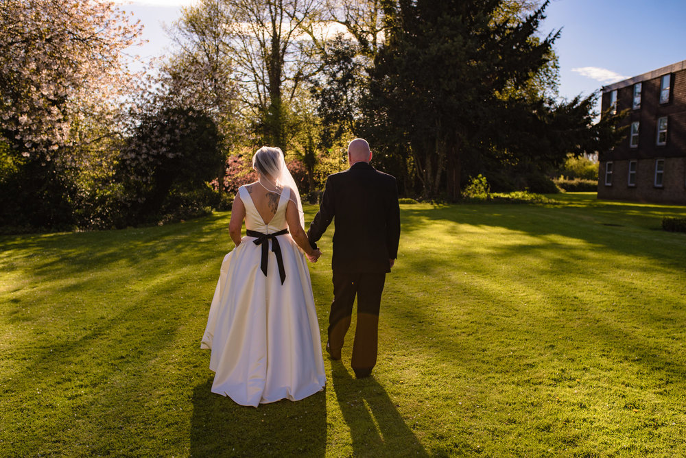 The Bride and groom walking in the grounds