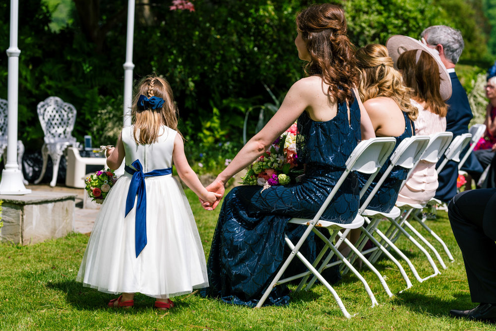 Bridesmaids and flower girl watch on