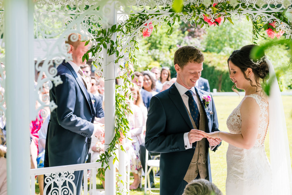 Groom puts the ring on his new wife