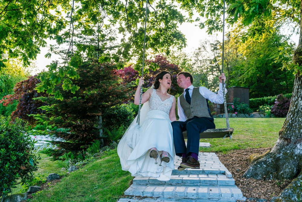 Bride and groom enjoying the swing in the garden