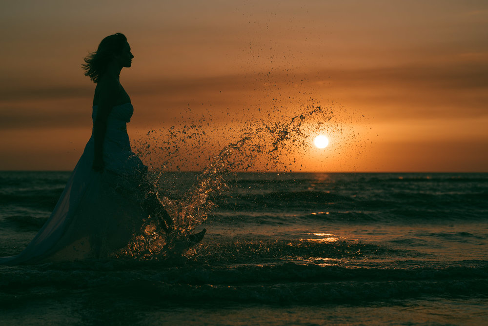 Bride in the sea, kicking up a splash
