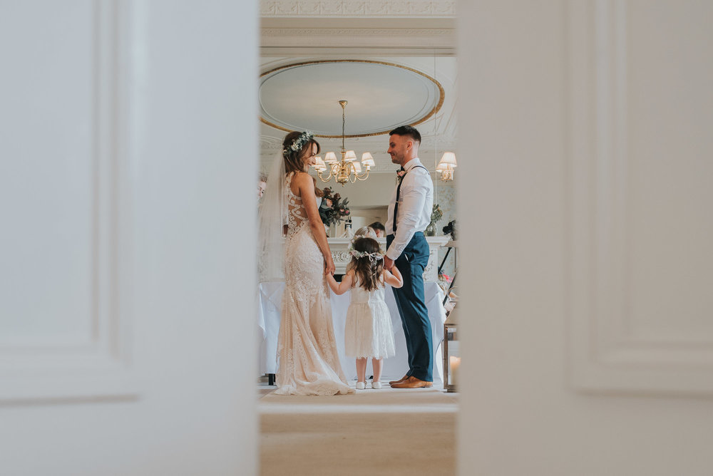 Through the door of the wedding ceremony room looking towards the bride and groom