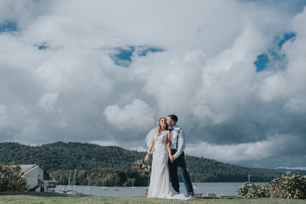 Bride and groom stand elevated above Lake Windermere