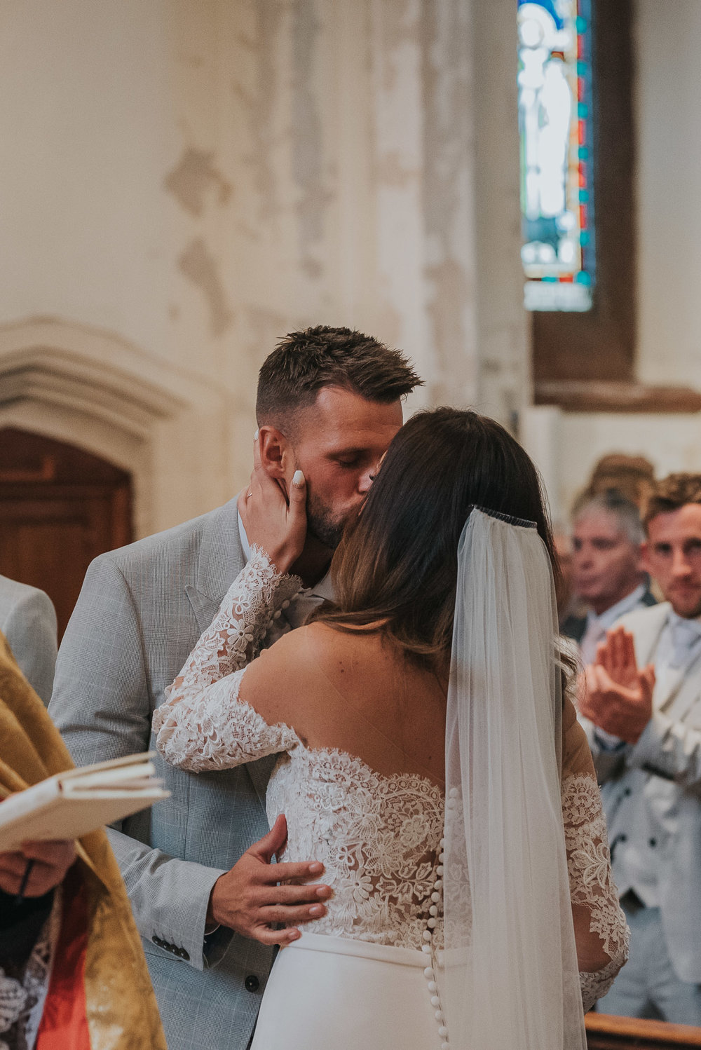 bride and groom share their first kiss in the church