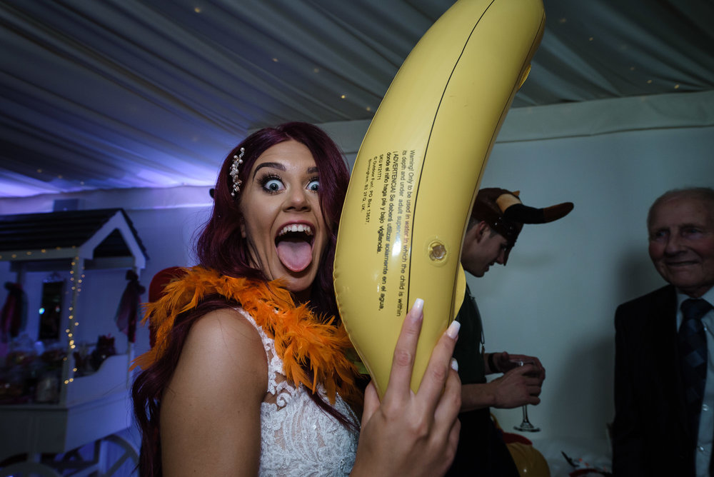 Crazy wedding guest holds an inflatable banana on the dance floor