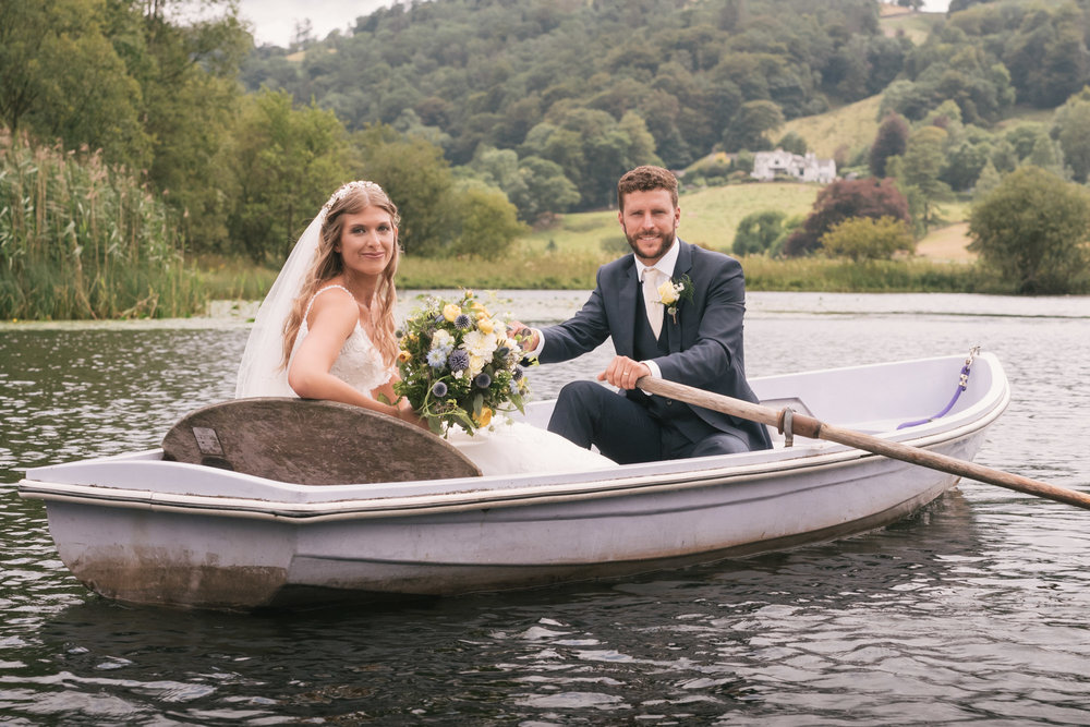 Bride and groom sitting in a rowing boat on their wedding day