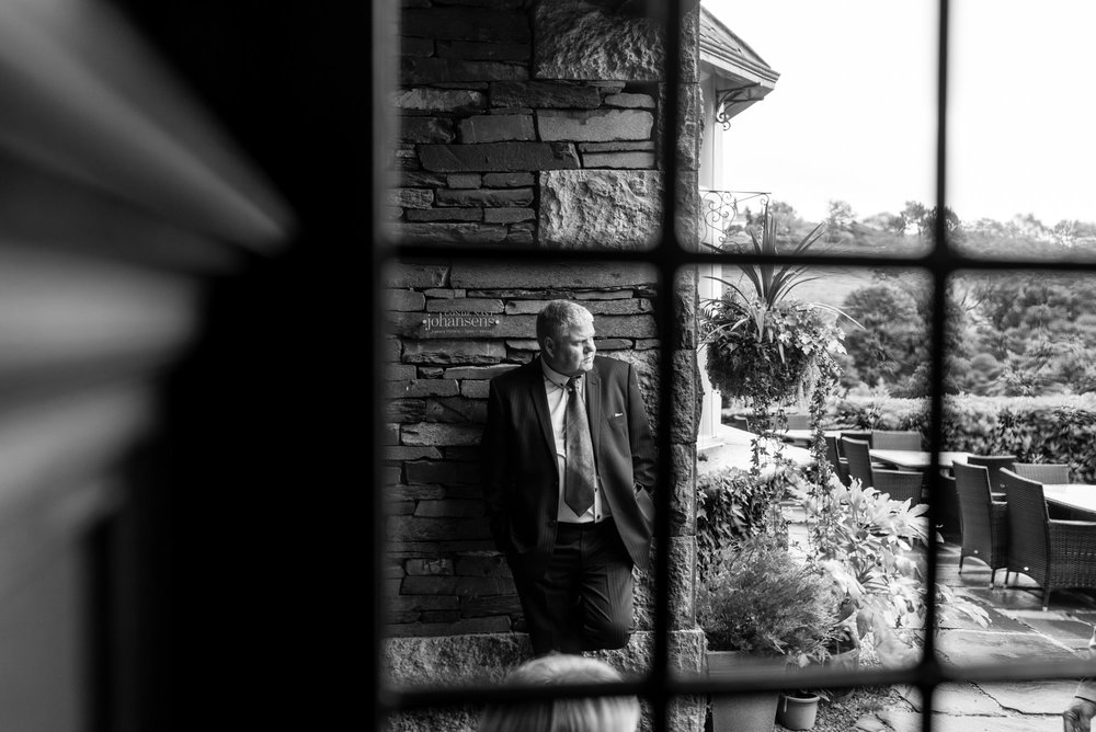 a wedding guest as viewed through the window of a lake district wedding