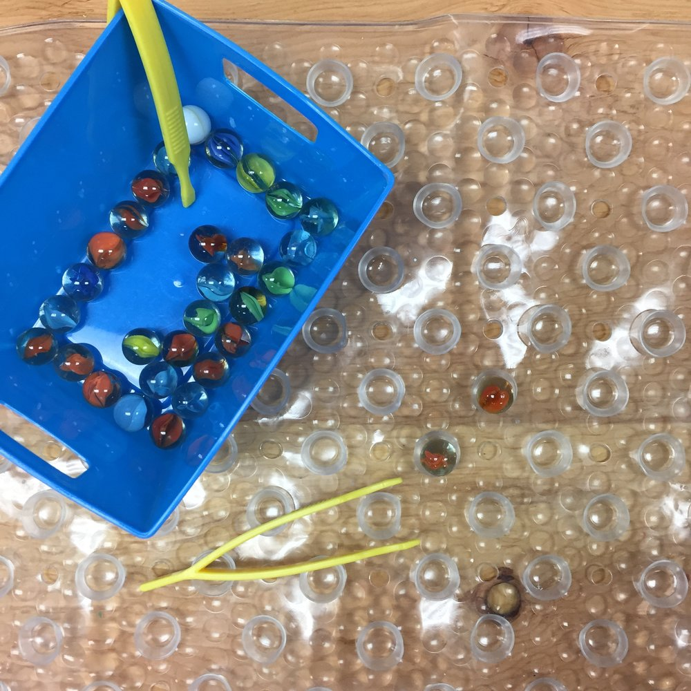 I love how this activity adds a fine motor element to play. This activity is very easy to prepare using materials that are inexpensive. All you need are tweezers, marbles and a rubber bath mat from the dollar store with suction cups on the bottom.  Just flip over the bath mat and students can place the marbles into the suction cup holes using the tweezers.
