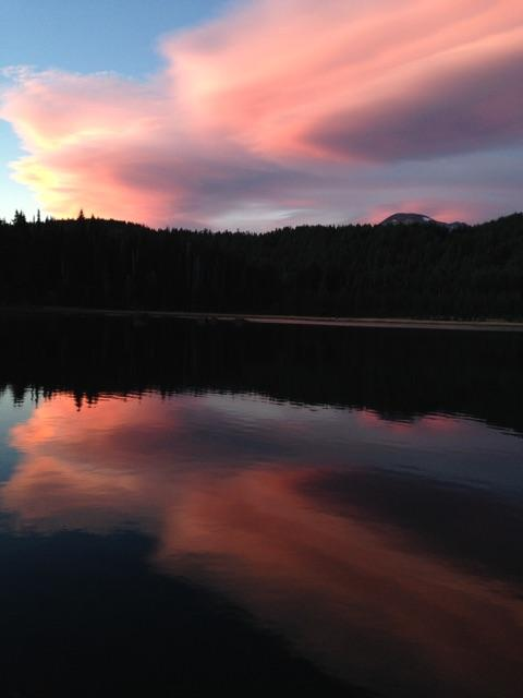 Pink sunset reflected in a mountain lake with dark trees in the background