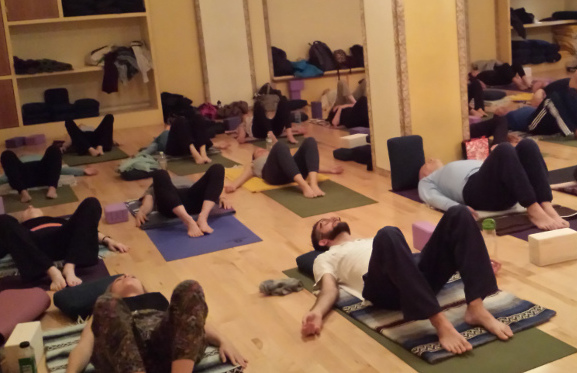 10 people laying on their backs with their feet on the floor and knees bent on yoga mats in a yoga studio