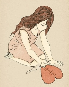 A girl with long brown hair is kneeling on the ground, sewing back together a large red heart that sits in front of her