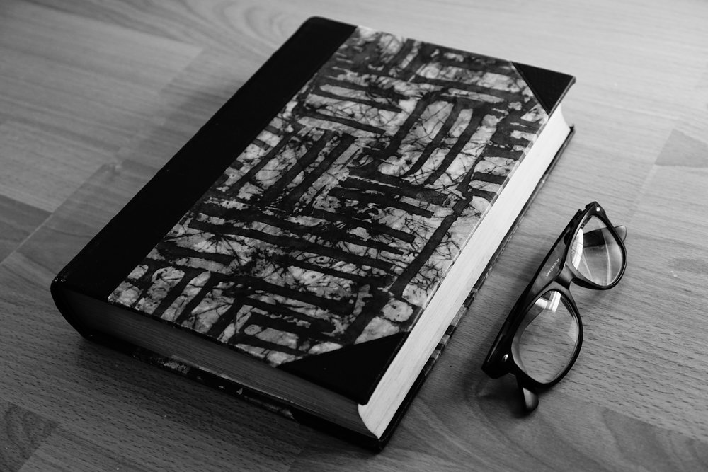 A black and white photo of a closed book with a abstract art cover sits next to a pair of black readig glasses on a woodend table.