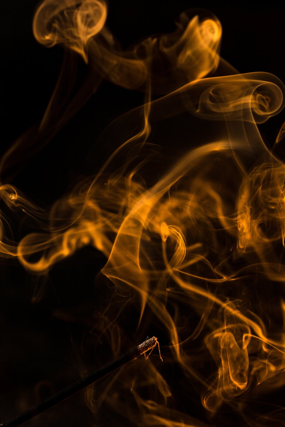 Whisps of orange smoke swirl against a black background