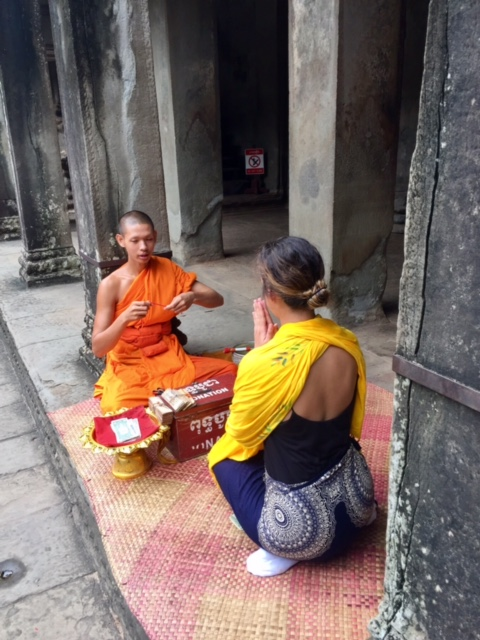 Ashlee receiving sai sin from a Buddhist monk inside of Angkor Wat.