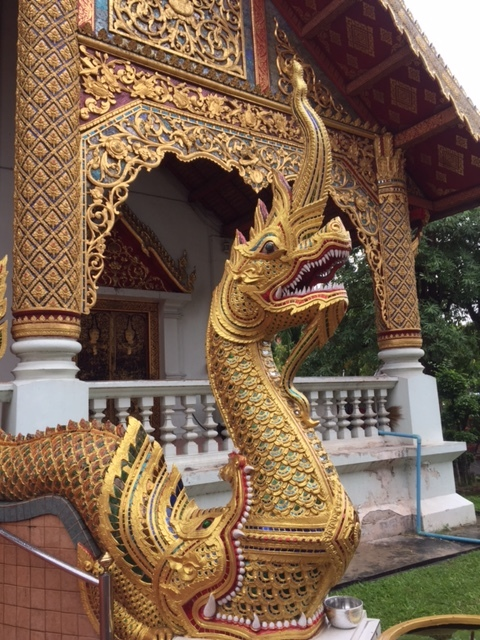 Statue of the mythical Naga Serpent guards the entrance to the Wiharn Luang prayer hall at Wat Phra Singh.