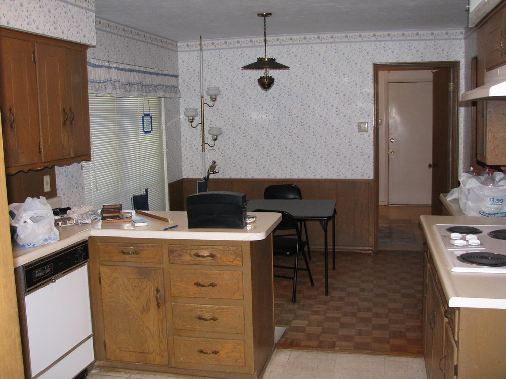 Kitchen before with worn cabinets, dated formica counters and 2 floor types