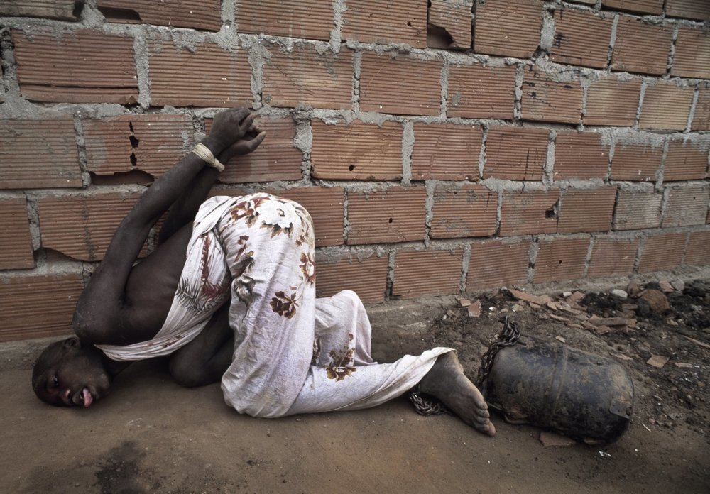A former combatant of Angola's long running civil war is chained to an engine  part at Papa Kitoko's mental asylum, Luanda, Angola, 1993