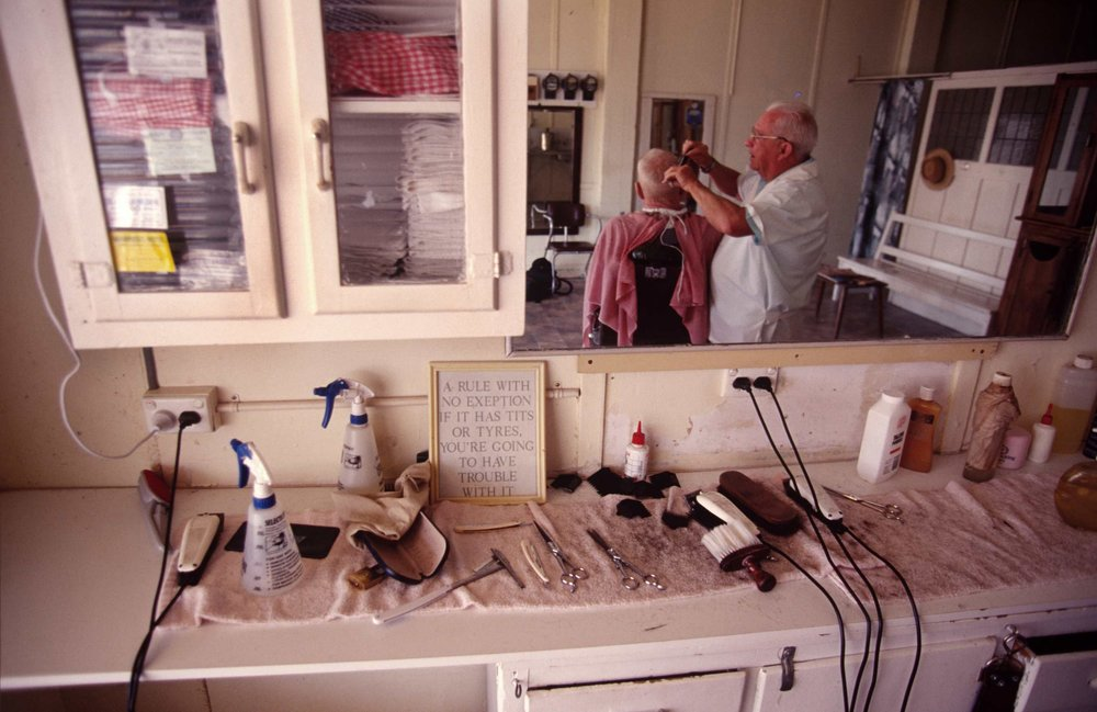Barber. Outback Queensland. Late 1980s Note: Photographer doesn't condone sentiments in picture frame.