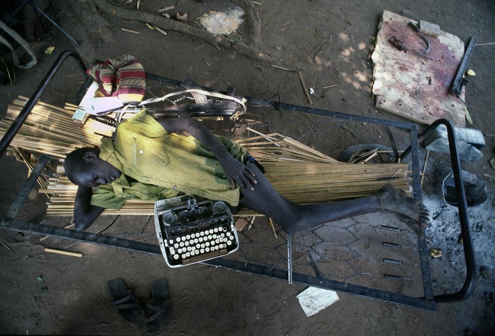 """""""Typewriter and Gun"""" A SPLA rebel soldier during downtime. During Sudan's long running civil war. 1993"""