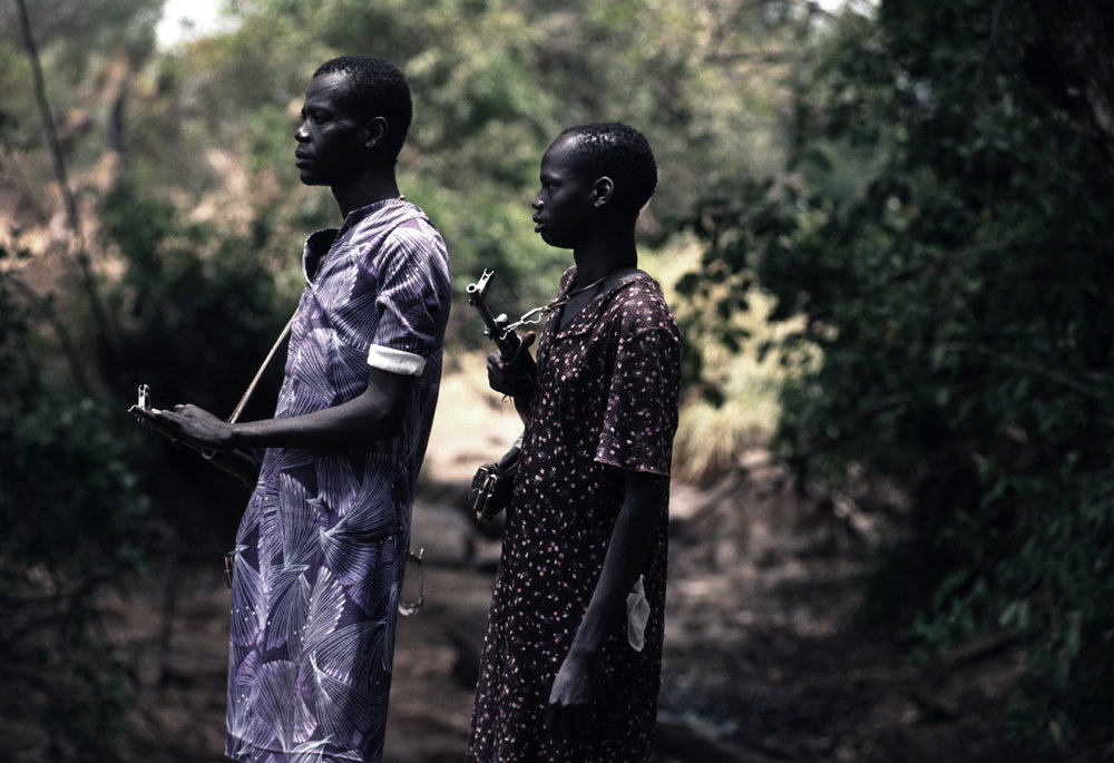 """Dresses and Guns"" Sometimes the SPLA were so challenged for war funds that they reverted to wearing civilian cloths. During Sudan's long- running civil war. 1993"