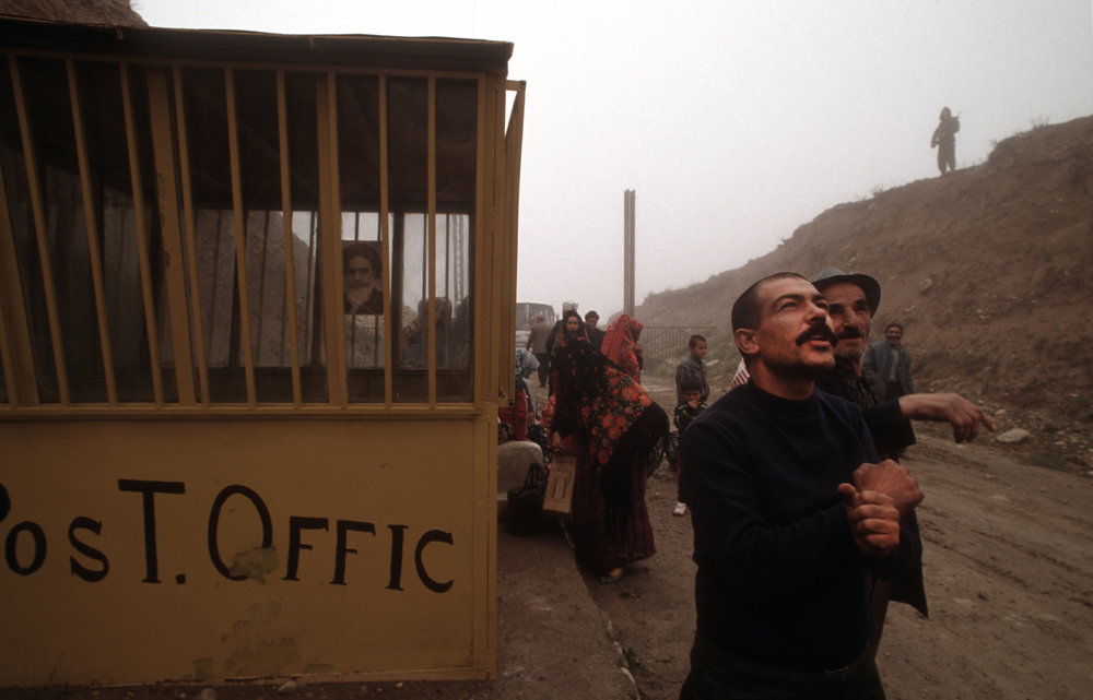 Turkmen leave Iran under the watchful gaze of Iranian military. On the border between Turkmenistan and Iran.  1992