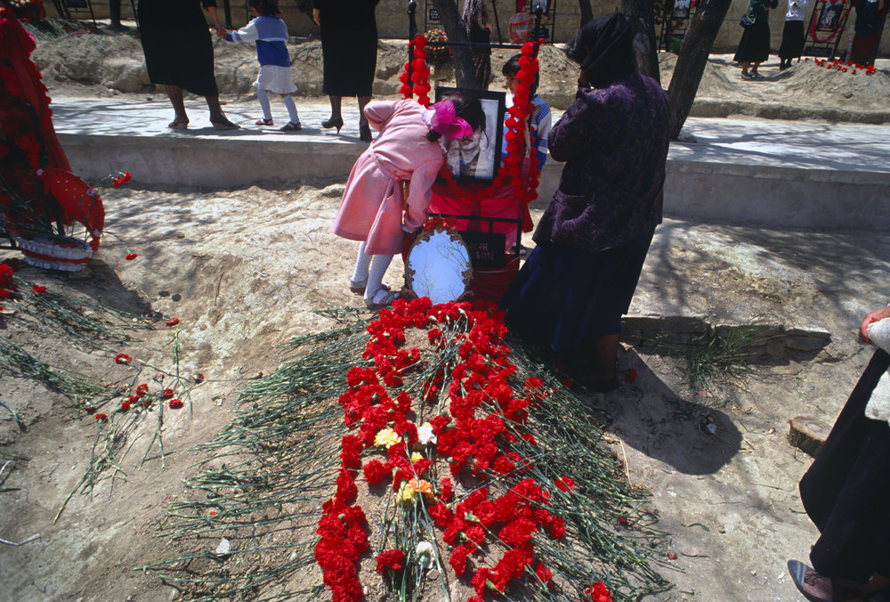 A child kisses a portrait of her father killed during the Nagorno-Karabakh War. Baku cemetery Azerbaijan. 1992