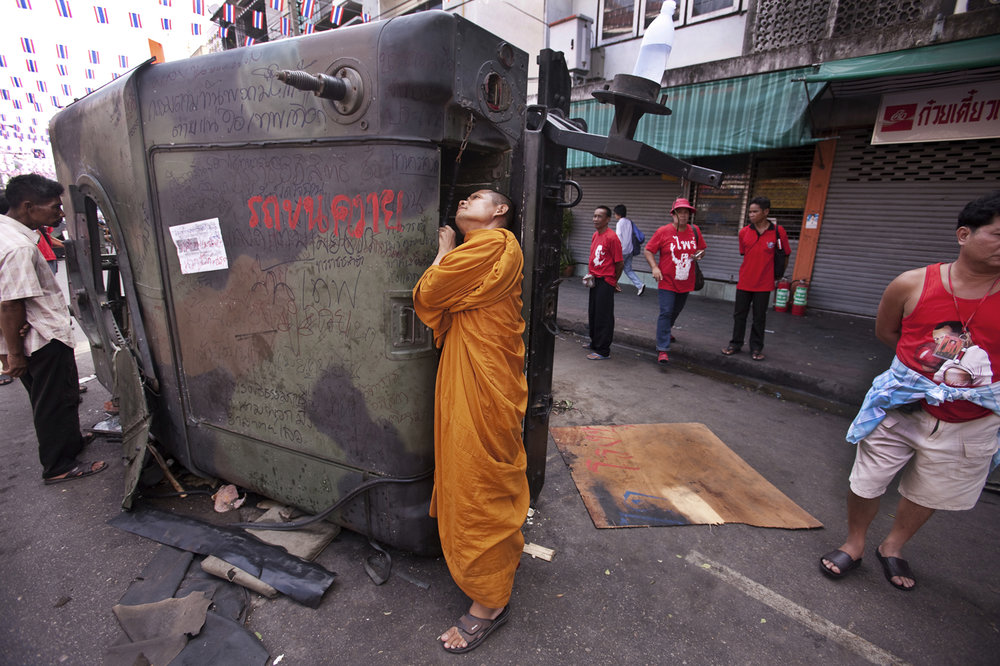"In 2010 in Bangkok at least 90 people died and more than 2,000 were wounded in clashes between the ""Red Shirts"" and the Thai military.  In This Photograph:  A Monk surveys a destroyed Thai Army APC near Khaosan Rd, Bangkok."