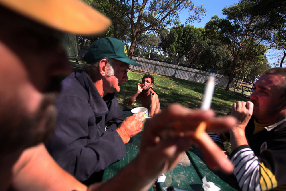 Tas (foreground and left), Dennis (Green baseball cap) drink with friends in a local park.