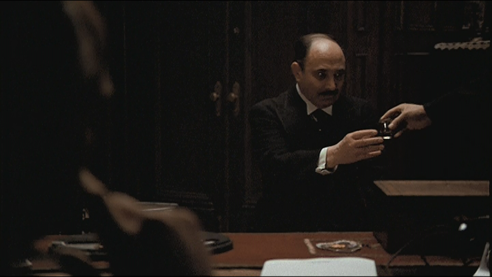 Minute 3: The Godfather-Expanding Scope - Amanda and Stephen dive head first into the glass of alcohol offered to Bonasera by a mystery figure. As the scope of the frame in the opening scene expands, they explore more elements of the film that are revealing themselves. From the production design to the time period the film is set in to the new people on screen that are just beginning to be revealed. Plus, there's discussion about the failings of the American court system.