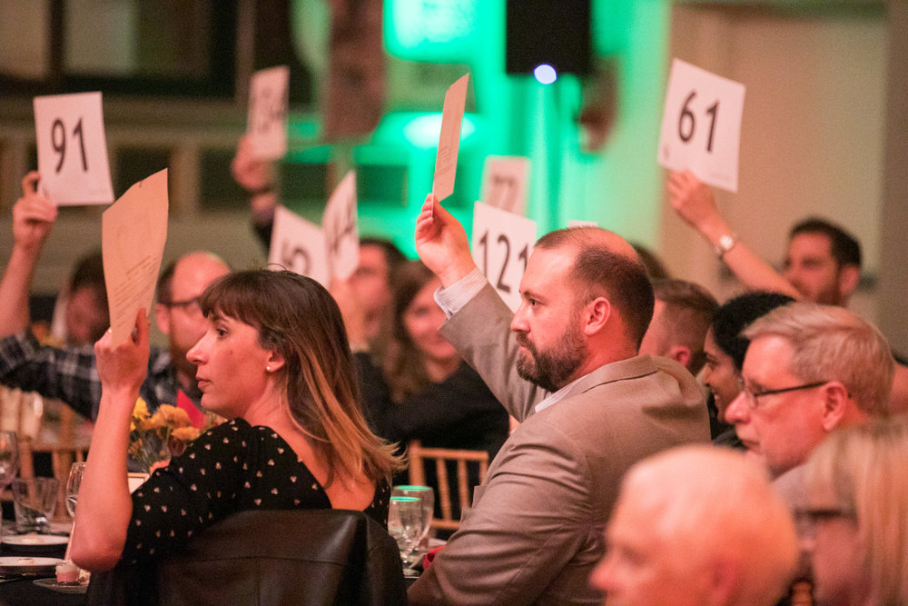 Attendees at the 2018 CROSO Benefit raising their paddles in support of our CROSO Scholars.