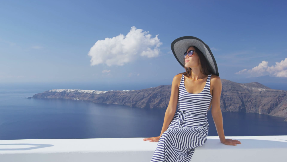 vacation-woman-enjoying-sun-elegant-on-luxury-travel-on-santorini-famous-europe-travel-destination-young-lady-living-fancy-jetset-lifestyle-wearing-dress-on-holidays-amazing-view-of-sea-and-caldera_slz - Copy.png