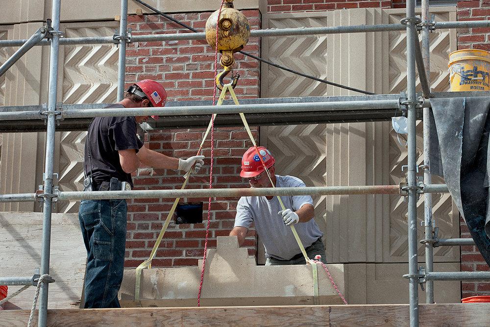 Consigli masons hoisting capstone onto parapet.jpg