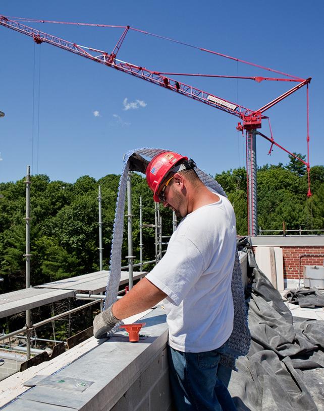 Consigli laborer installing drainage mat at parapets.jpg