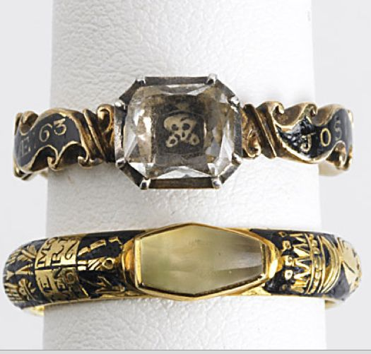 Ring 1 (top) - gold, black enamel with names and dates of the deceased, a painted skull with a diamond set on top. Ring 2 (bottom) - A precious stone cut in to the shape of a coffin, with dates, names and skulls outlined in gold and black enamel.