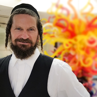 Rabbi Yom Tov Glaser - He was born in Hollywood, California and traveled around the world looking for extreme places to go surfing and mountain biking. A lover of music, he has been playing music professionally for over two decades. In England, he's known as the Jewish Bob Marley! Throughout his journey, he accumulated vast insights into human character, religion and alternative spirituality. After receiving a Bachelor of Arts from the University of California in Santa Barbara, he moved to Israel to explore Judaism at Aish HaTorah. After six years of intense study, he became a Rabbi. Today, Rav Yom Tov lives with his family in Yerushalyim where he practices spiritual therapy and runs the renown