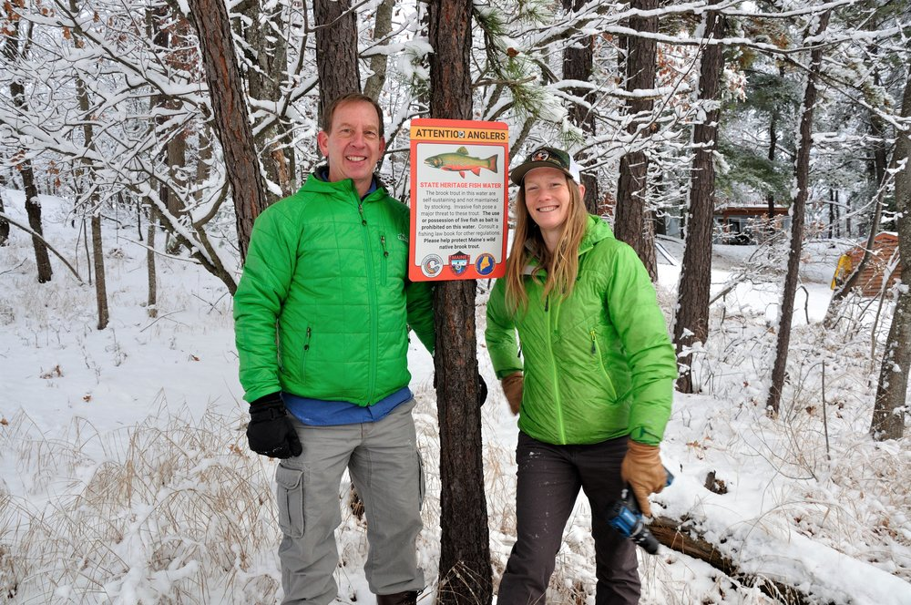 Maine Audubon Executive Director Andrew Beahm and Maine NFC Chair Emily Bastian posting a State Heritage Fish water sign in York County, Maine.