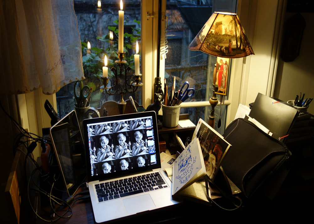 My crowded writing desk at dawn by candlelight.